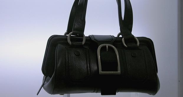 S černou kabelkou černé boty.