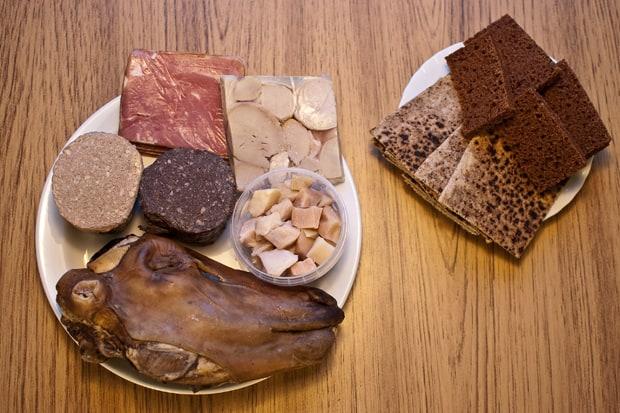 Vlevo: uzené jehněčí maso, tlačenka z beraních varlat, klobása z ovčích jater, krvavý puding (jelito), kostky žraločího masa, ovčí hlava. Vpravo: žitný chléb a chlebové placky.